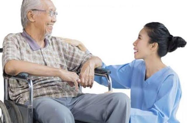 perawat yang sedang berkomunikasi dengan lansia