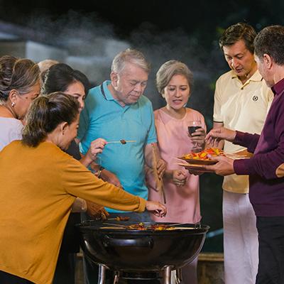 sekelompok senior sedang bersosialisasi dan bersengang-senang barbeque