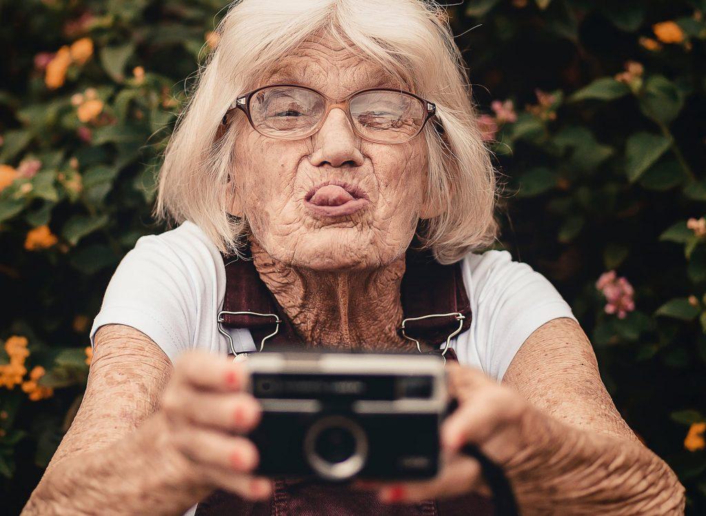 senior sehat dengan latar belakang bunga sedang memegang kamera