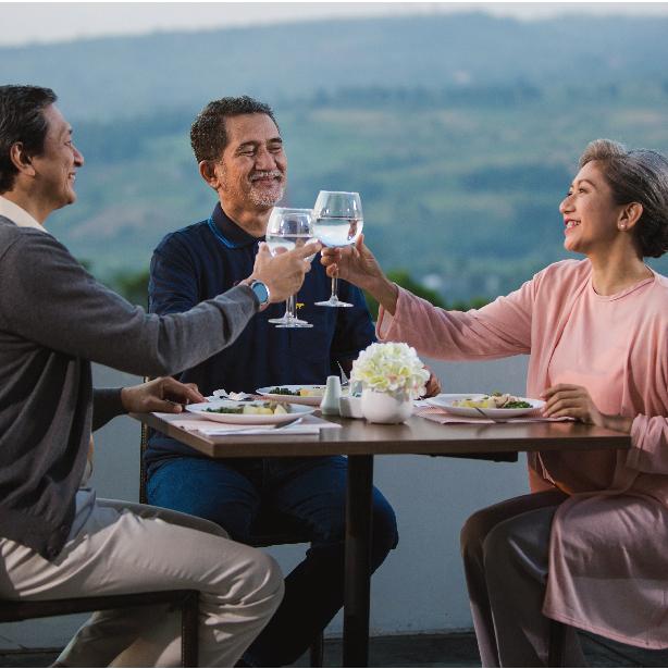 tiga orang senior sedang bersantai dan bersulang di senior friendly hotel & resort