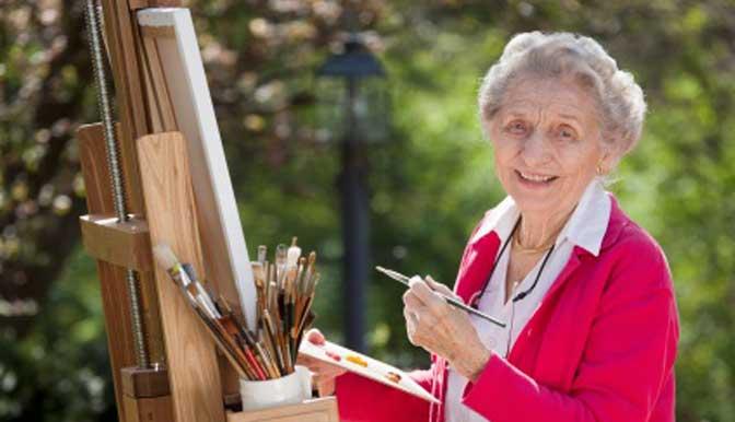 senior lansia berbaju merah sedang melukis untuk menunjang hobi dan kebahagiaan lansia